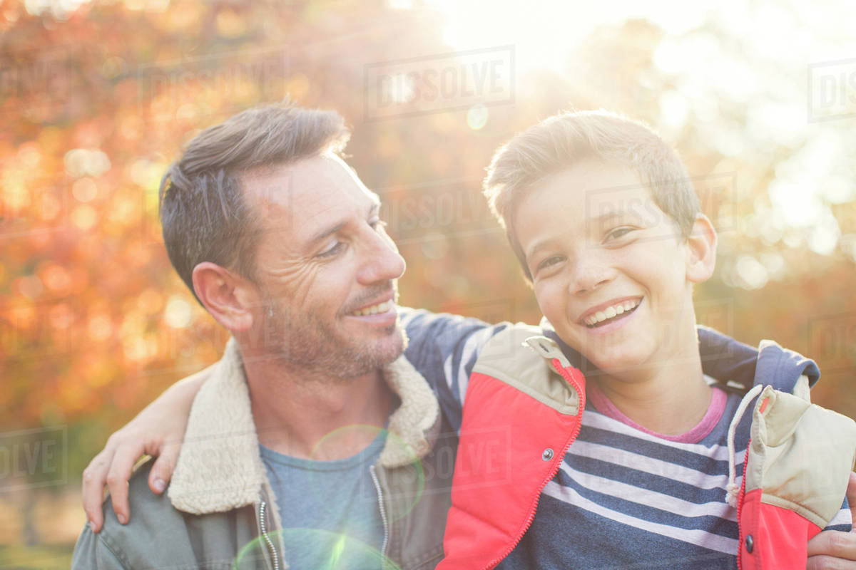 Portrait smiling father and son in front of autumn leaves Royalty-free stock photo