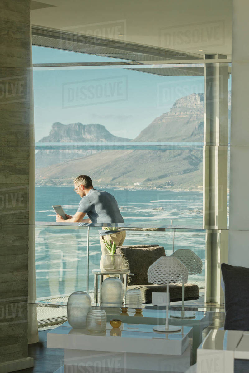 Reflection of man using digital tablet on luxury balcony with ocean and mountain view Royalty-free stock photo