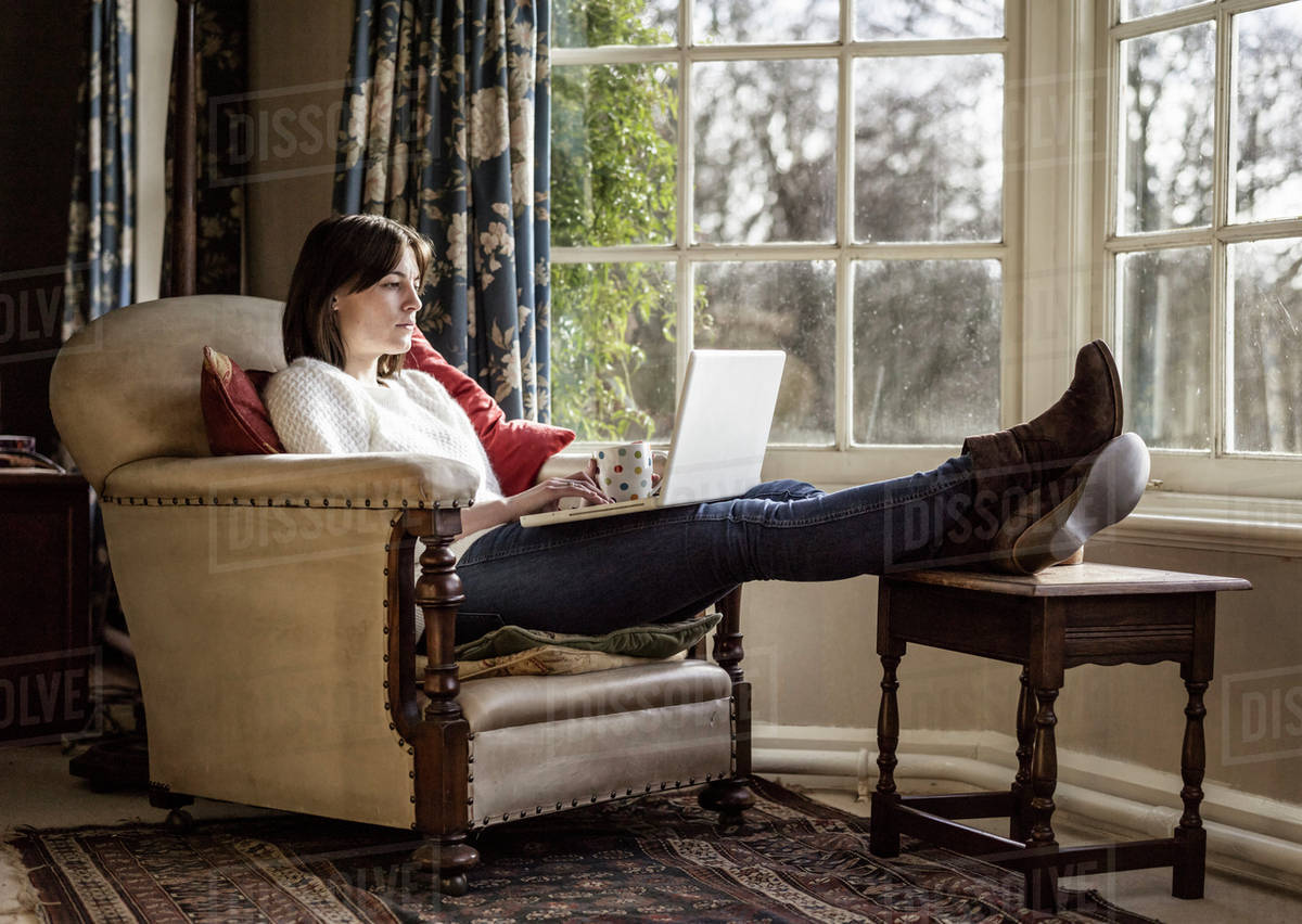 a young woman relaxing at home with her feet up using a. Black Bedroom Furniture Sets. Home Design Ideas