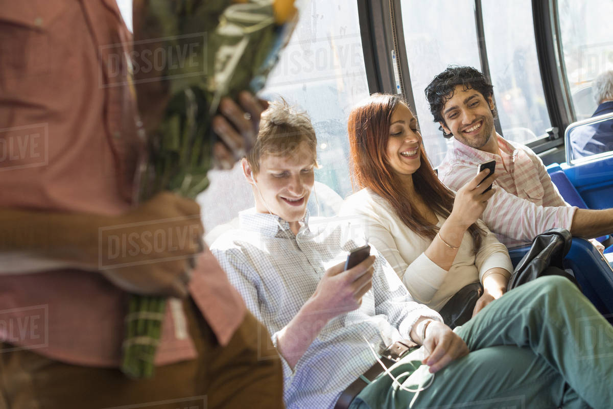 Urban Lifestyle. A group of people, men and women on a city bus, in New York city. Two people checking their phones. One man standing holding a bunch of flowers. Royalty-free stock photo