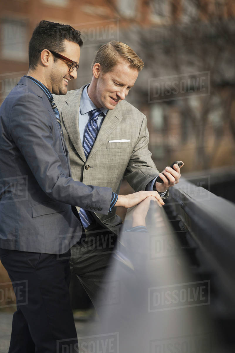 Two men in formal business clothes, standing side by side, looking at a cell phone screen or mobile phone. Royalty-free stock photo