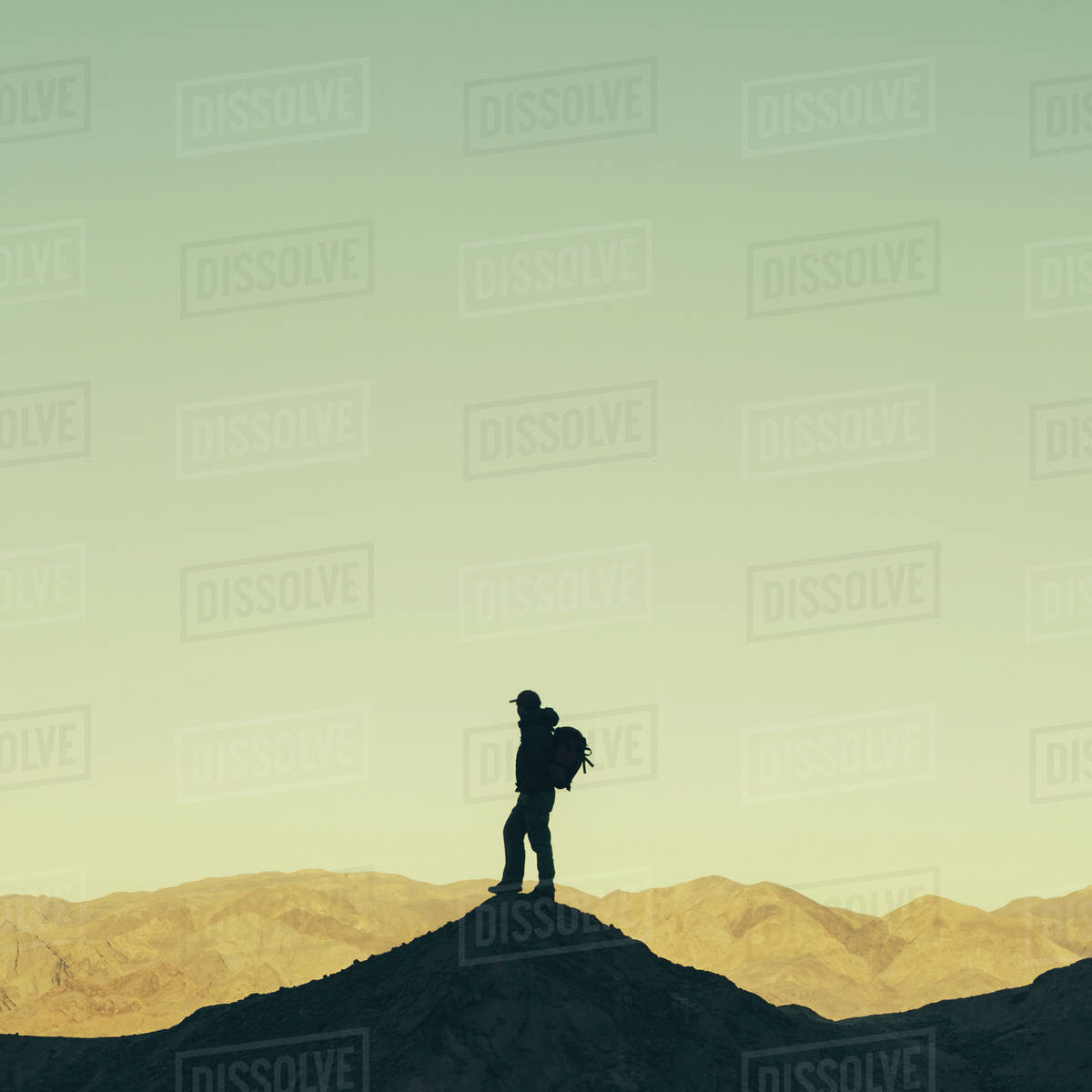 Silhouette of a male hiker wearing a backpack and standing on a hilltop in Death Valley national park. Royalty-free stock photo