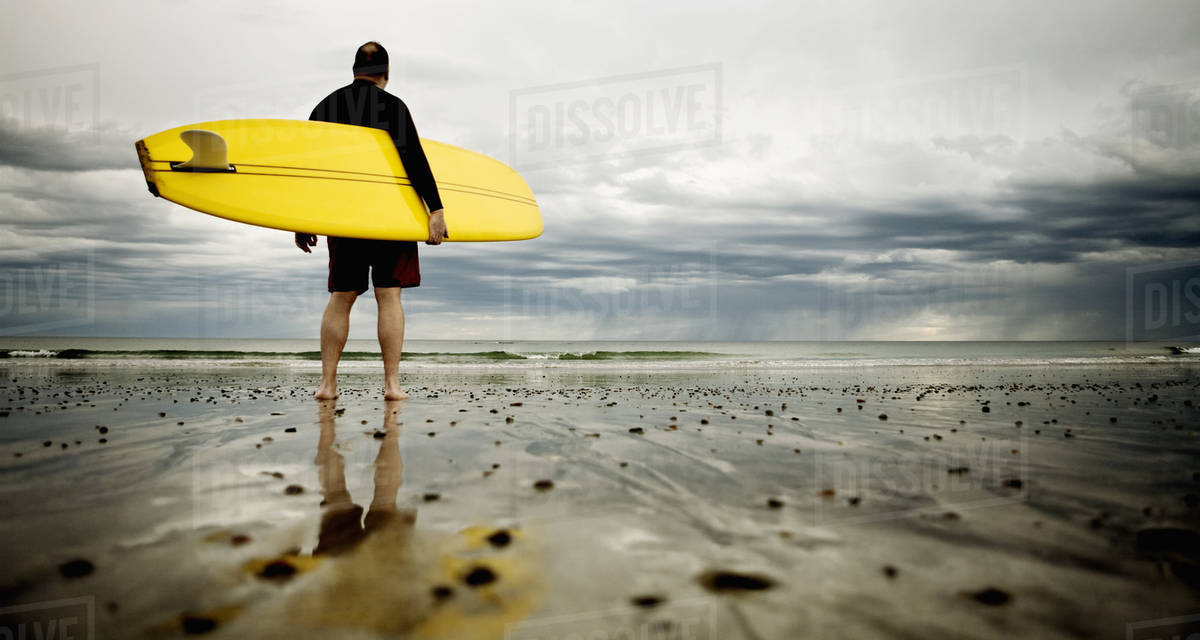 A middle aged man surfing in New England on Rockport Beach.  Royalty-free stock photo