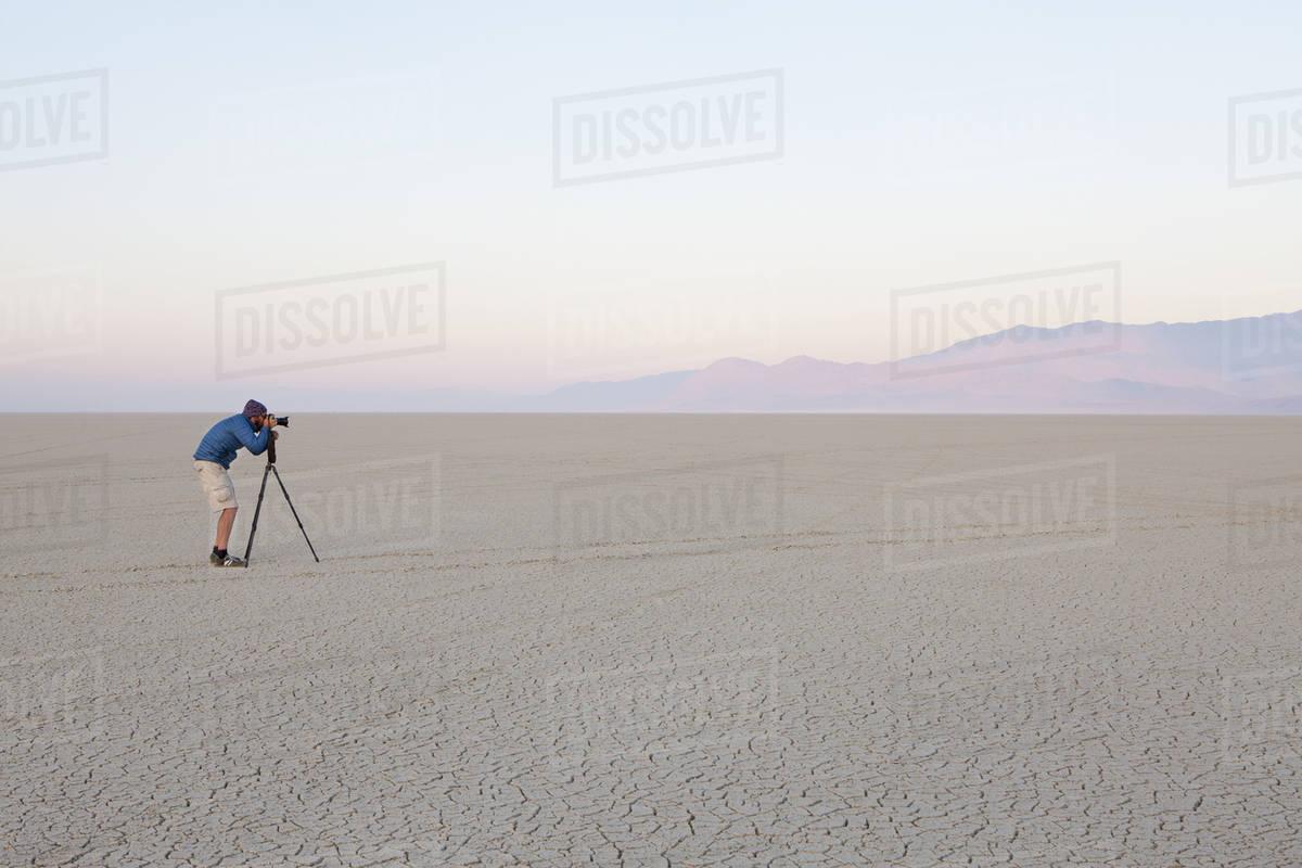 Man with camera and tripod on the flat saltpan or playa of Black Rock desert, Nevada. Royalty-free stock photo