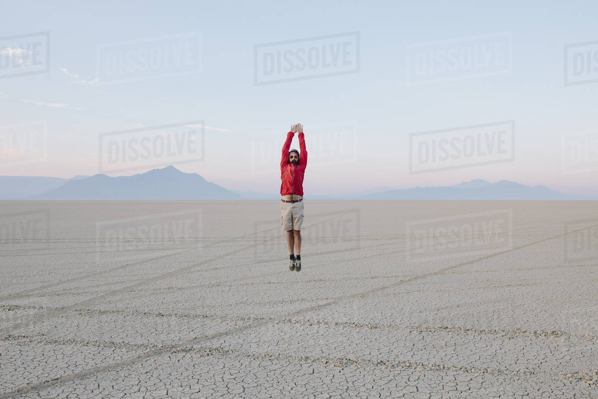A man jumping in the air on the flat desert or playa or Black Rock Desert, Nevada.  Royalty-free stock photo