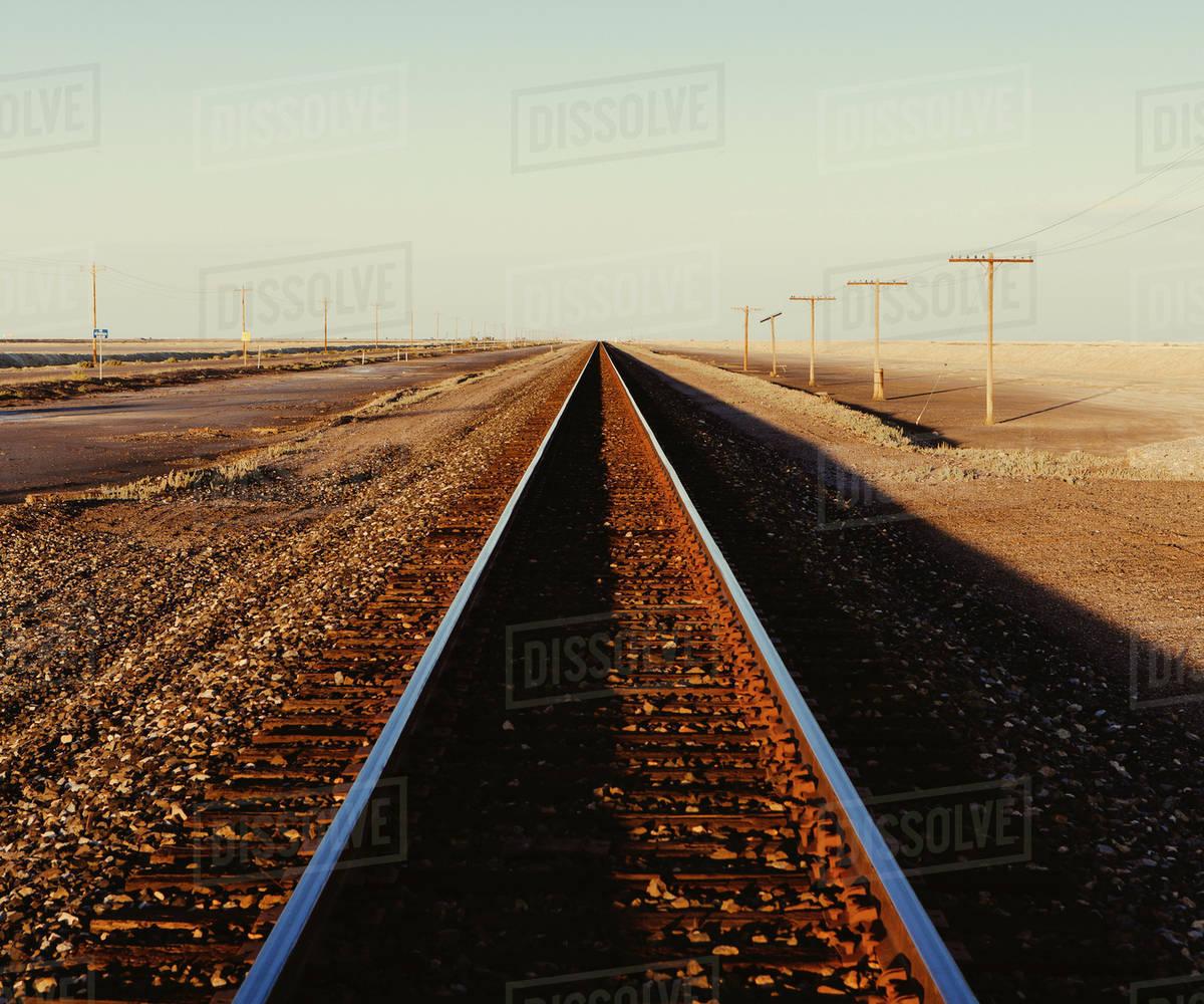 Railroad tracks extending across the flat Utah desert landscape, at dusk.   Royalty-free stock photo