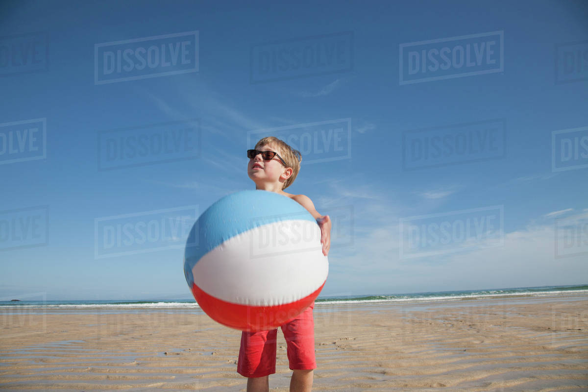 A boy on the beach holding a large inflatable beach ball.  Royalty-free stock photo