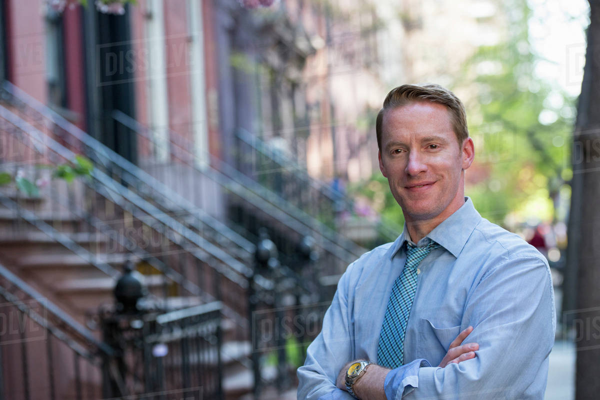 A Man In A Blue Shirt And Blue Tie With Arms Folded, Standing On The Sidewalk Royalty-free stock photo