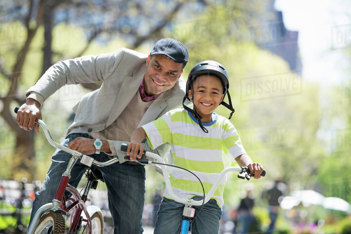 A Family In The Park On A Sunny Day. Father And Son Bicycling Royalty-free stock photo