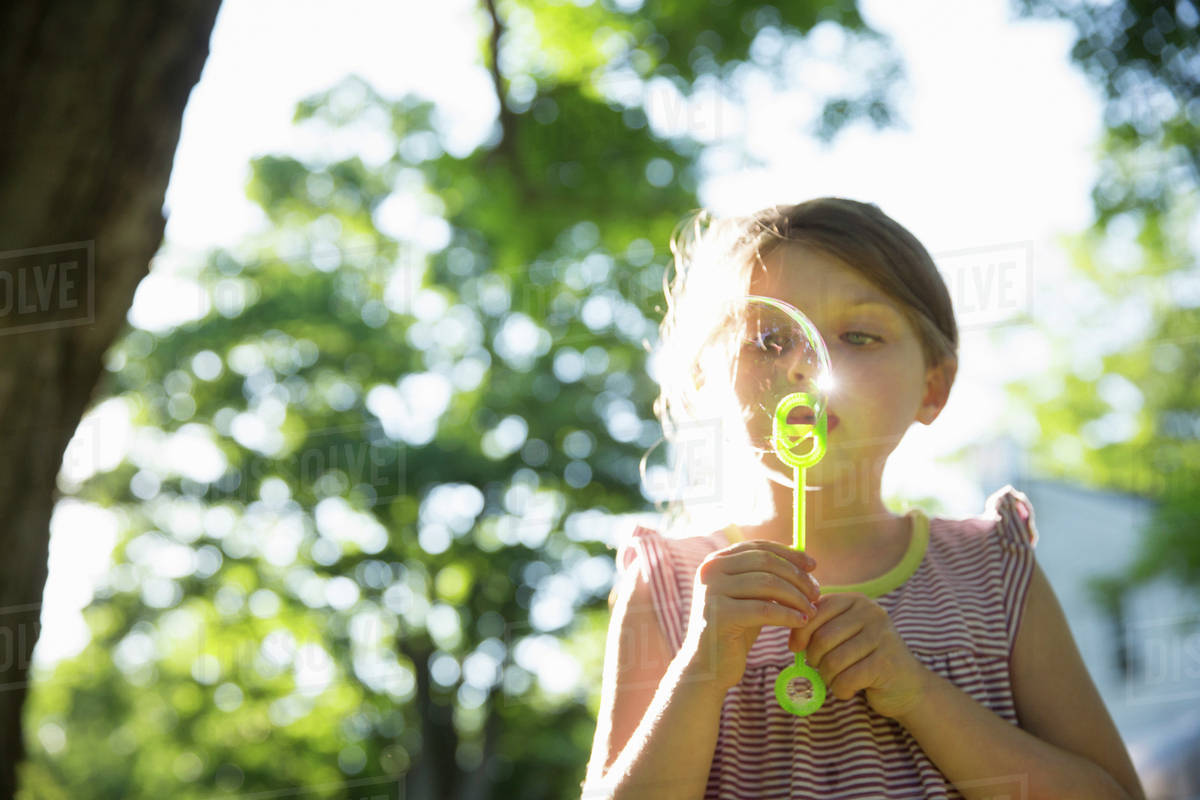 Outdoors In Summer. A Young Girl Blowing Bubbles In The Air Under The Branches Of A Large Tree.  Royalty-free stock photo