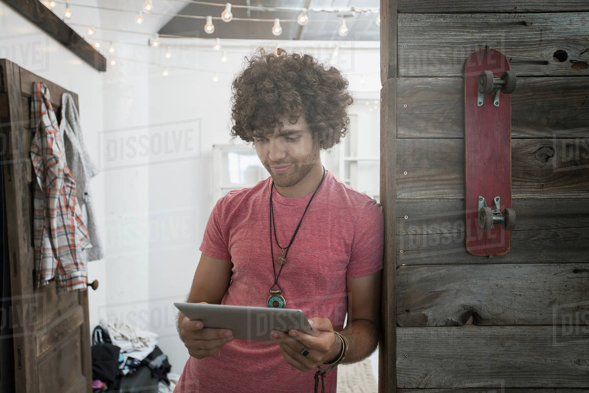 Loft living. A young man standing looking at a digital tablet.  Royalty-free stock photo