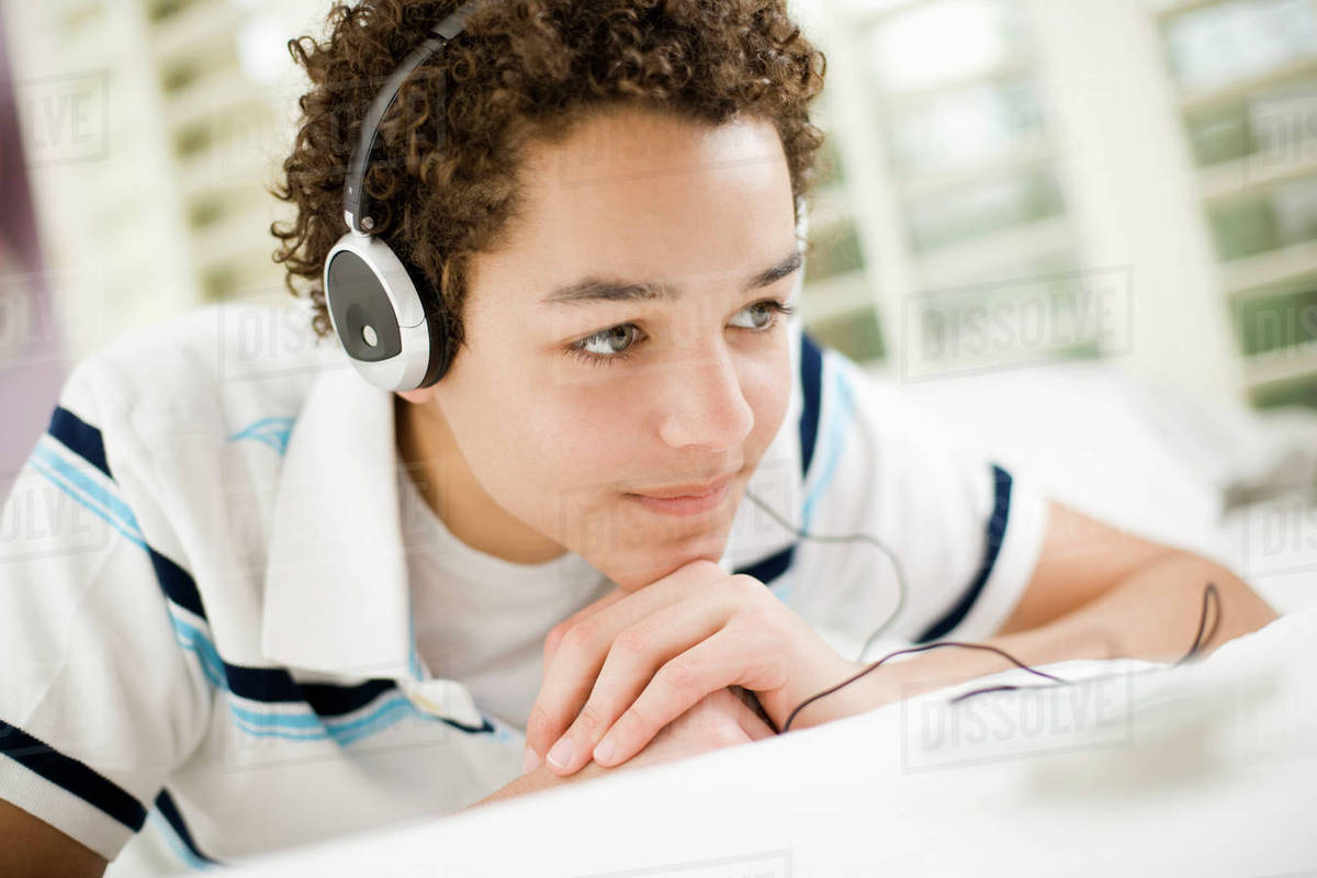 A boy wearing headphones lying on his stomach.  Royalty-free stock photo