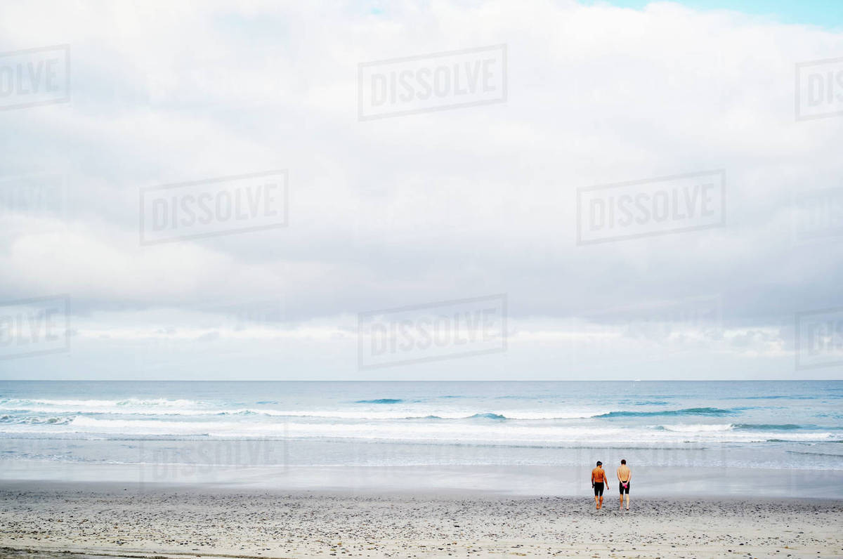 Two men standing on a sandy beach by the ocean. Royalty-free stock photo