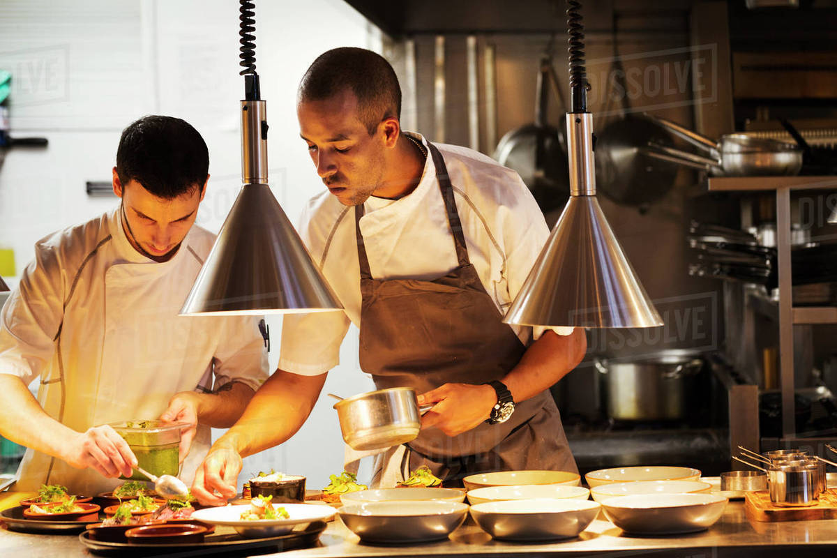 two chefs standing in a restaurant kitchen plating food royalty free