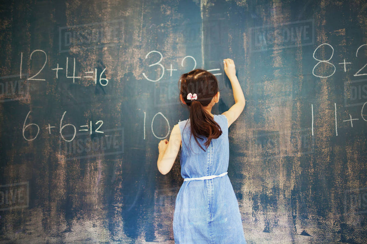 A group of children in school. A girl writing in chalk on a chalkboard. Royalty-free stock photo
