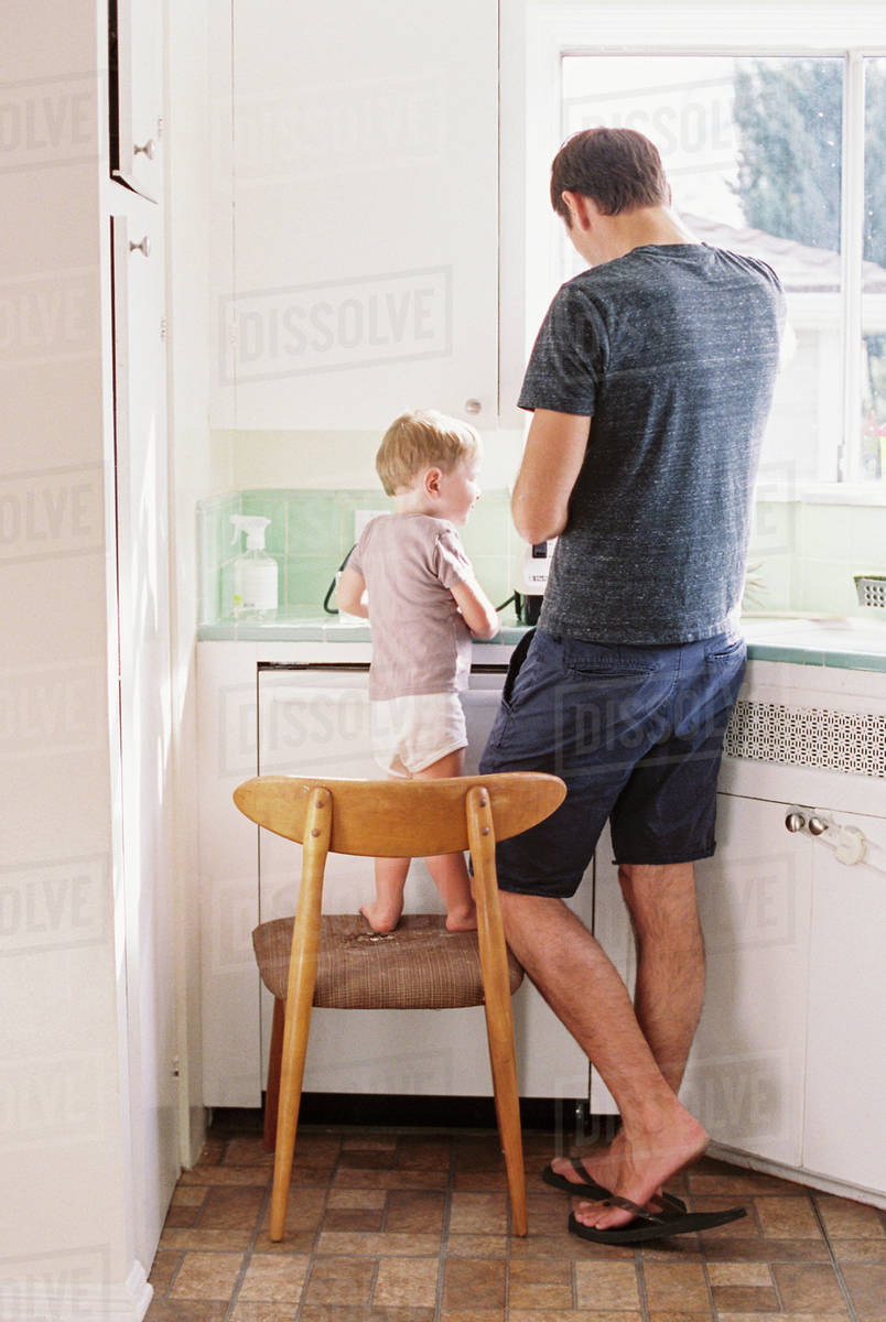 Man standing in a kitchen, his son standing on a chair beside him. Royalty-free stock photo