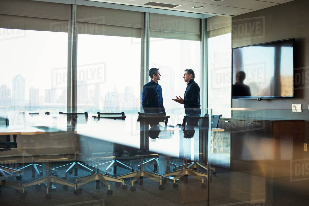 Two men standing at a table in a meeting room talking to each other. Royalty-free stock photo