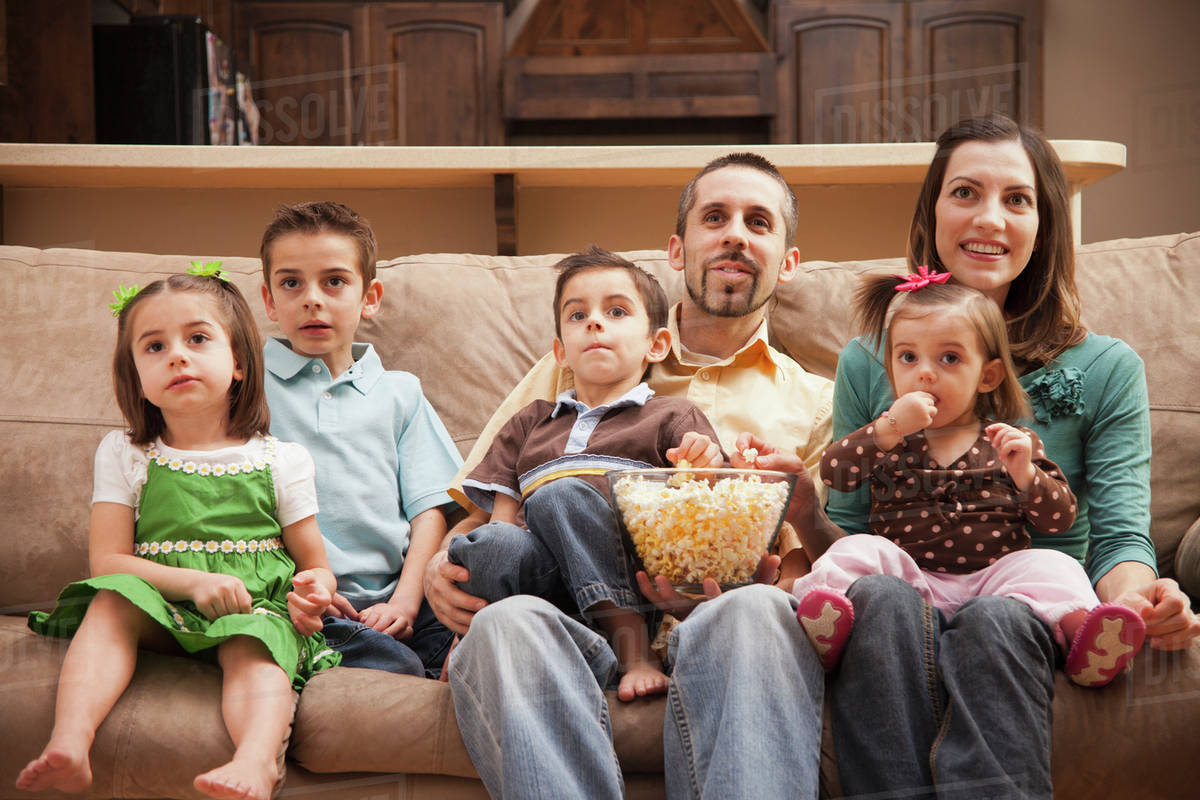 kids watching tv and eating. front view of family with children (18-23 months, 4-5, 6-7, 8-9) sitting on couch watching tv and eating popcorn kids