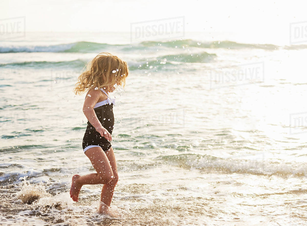Girl (4-5) running in water on beach Royalty-free stock photo