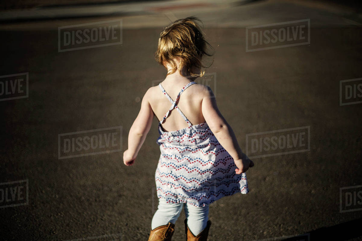 Rear view of girl standing on road Royalty-free stock photo