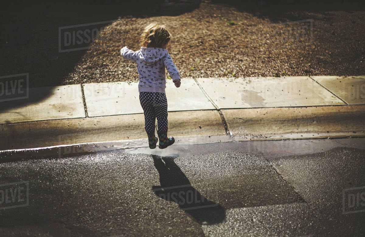 Rear view of girl playing on wet road on sunny day Royalty-free stock photo