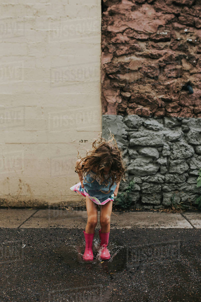 Playful girl jumping in puddle on road against wall Royalty-free stock photo