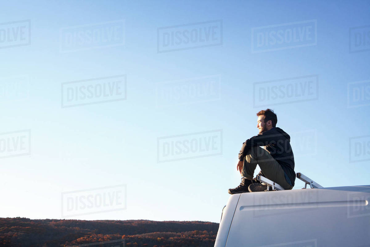 Side view of thoughtful man sitting on camper van Royalty-free stock photo