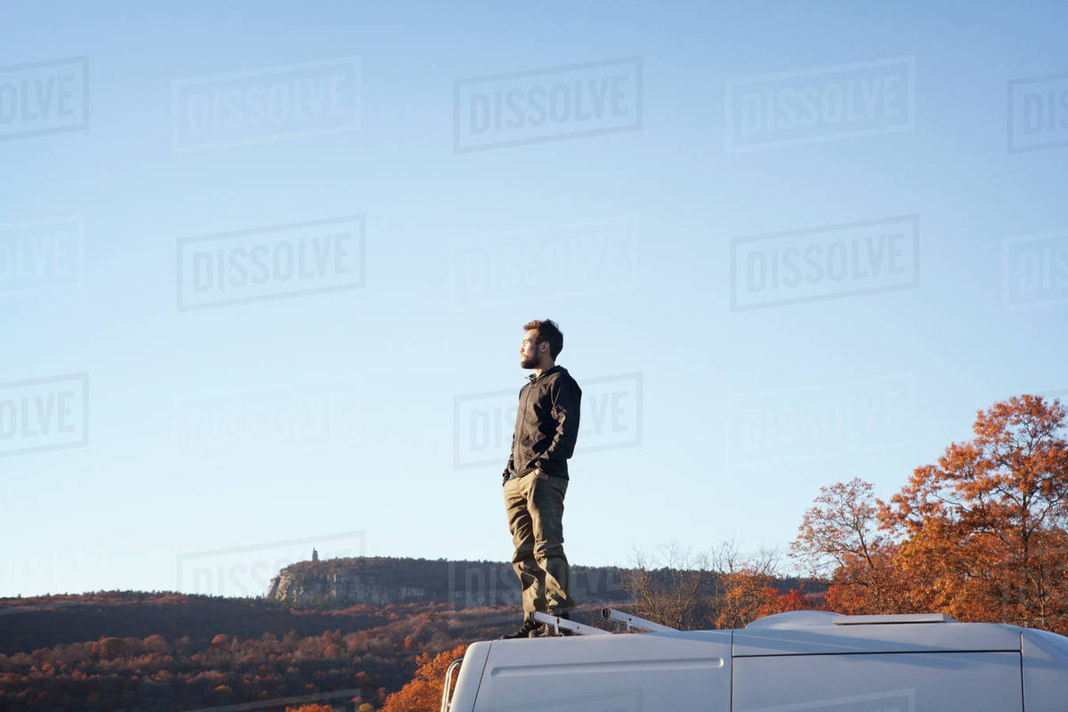 Man with hands in pocket standing on camper van against clear sky Royalty-free stock photo
