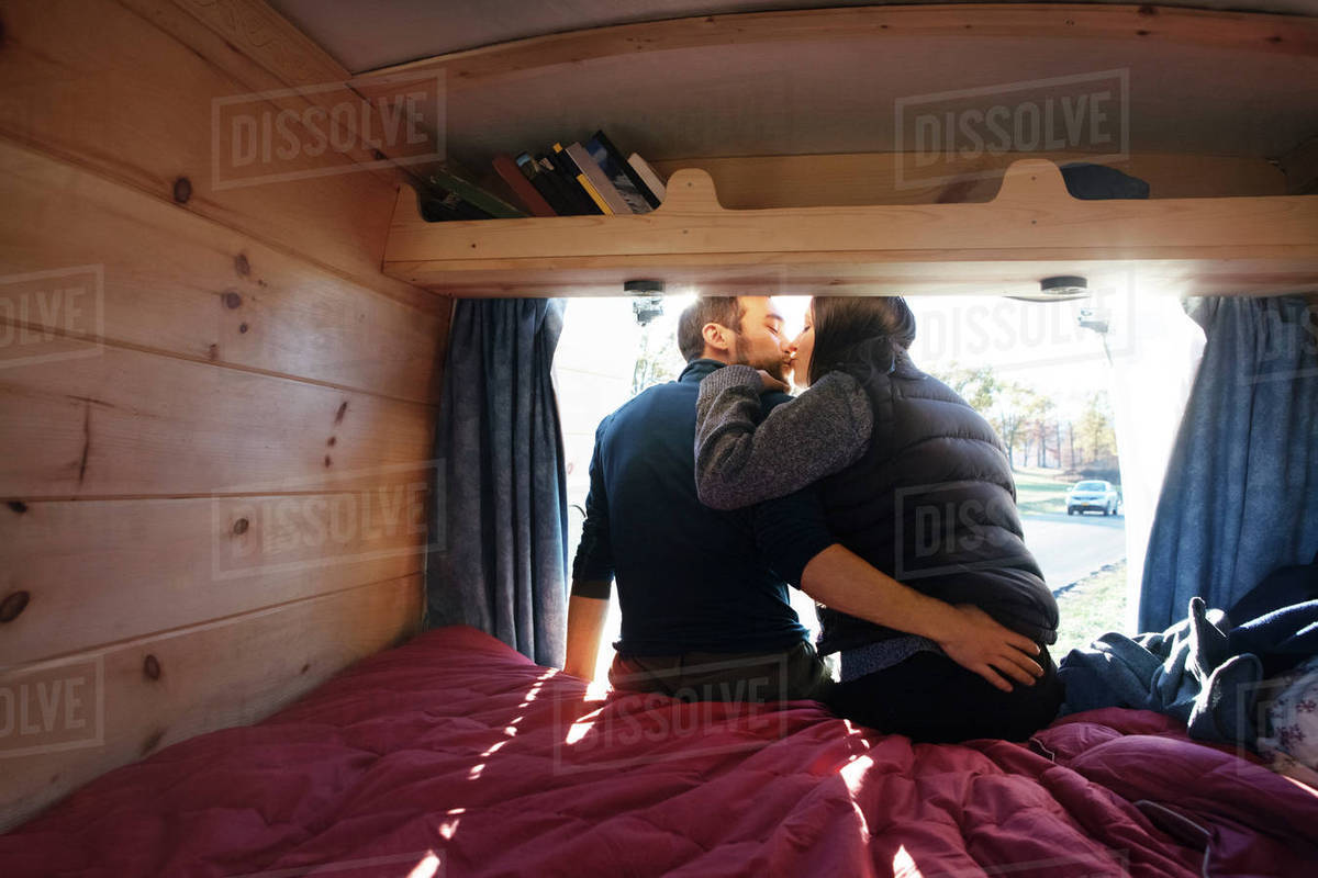 Rear view of couple kissing while sitting on bed in camper van Royalty-free stock photo