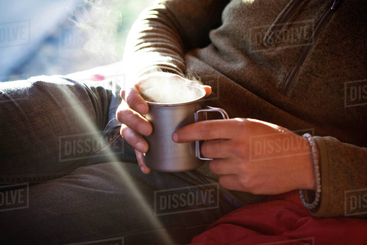 Midsection of man holding dink while sitting on bed in camper van Royalty-free stock photo