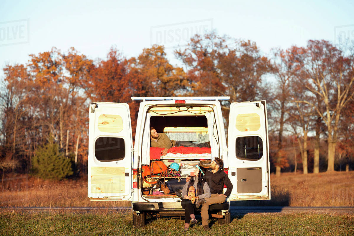 Couple looking at friend relaxing in camper van Royalty-free stock photo
