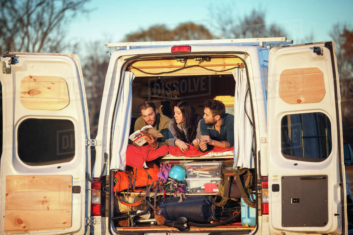 Couple looking at friend reading book while relaxing on bed in camper van Royalty-free stock photo