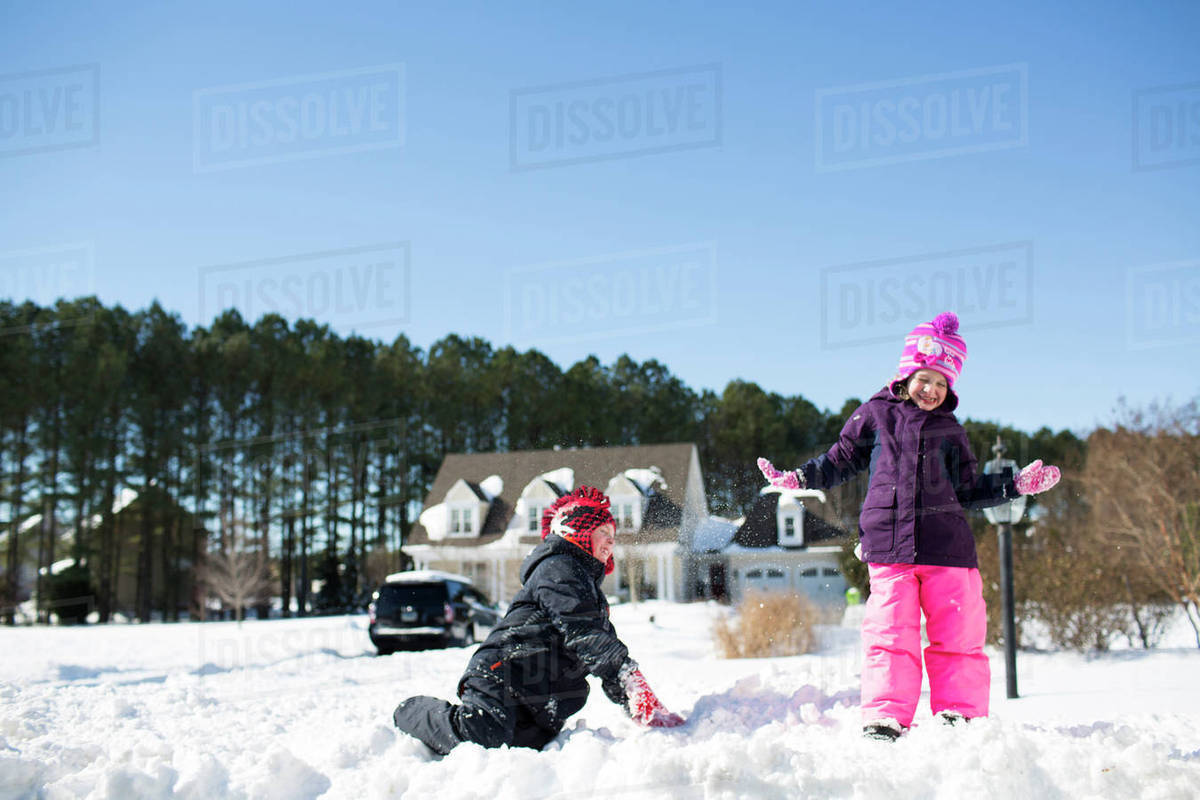 Siblings playing with snow on field against clear blue sky Royalty-free stock photo