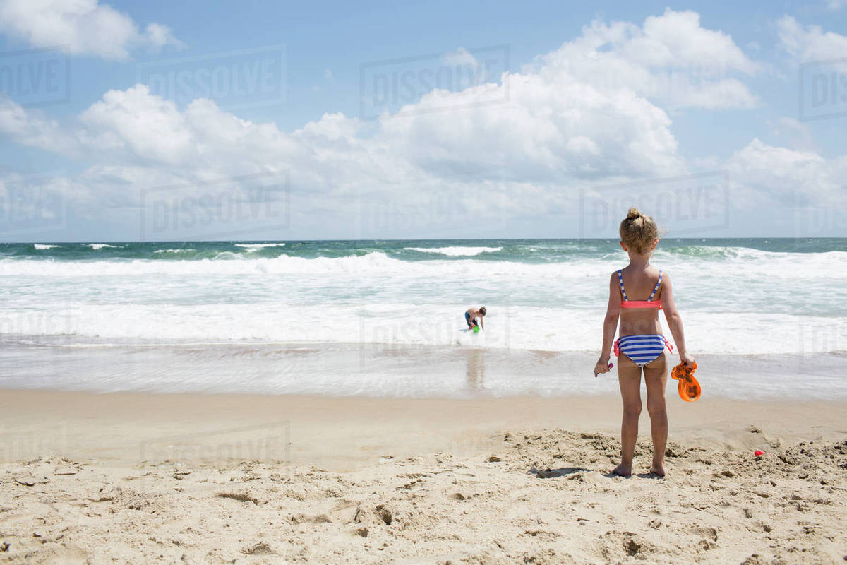 Rear view of girl looking at brother playing in sea against cloudy sky Royalty-free stock photo