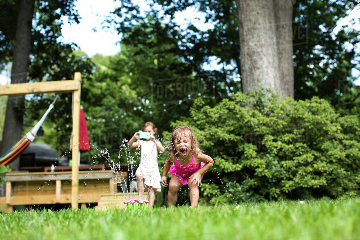 Girl photographing while sister playing with sprinkler in backyard Royalty-free stock photo