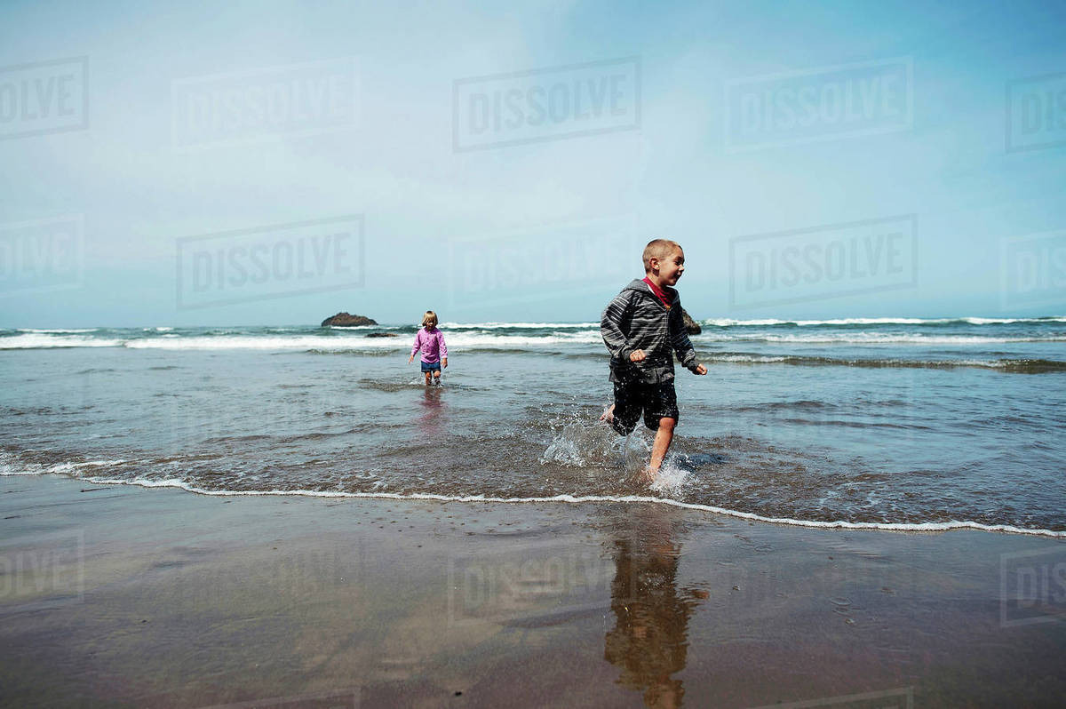 Siblings playing in sea against sky during sunny day Royalty-free stock photo