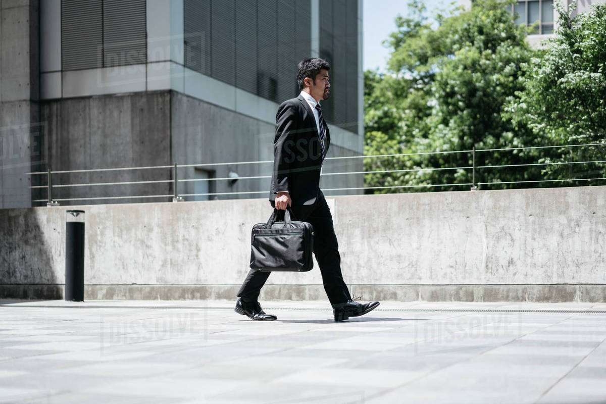 Full length side view of businessman carrying briefcase while walking on bridge in city Royalty-free stock photo
