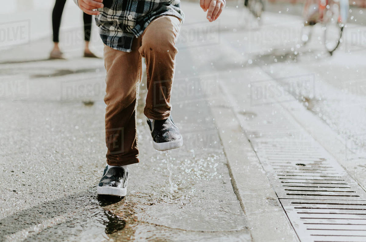 Low section of boy jumping on puddle at street Royalty-free stock photo