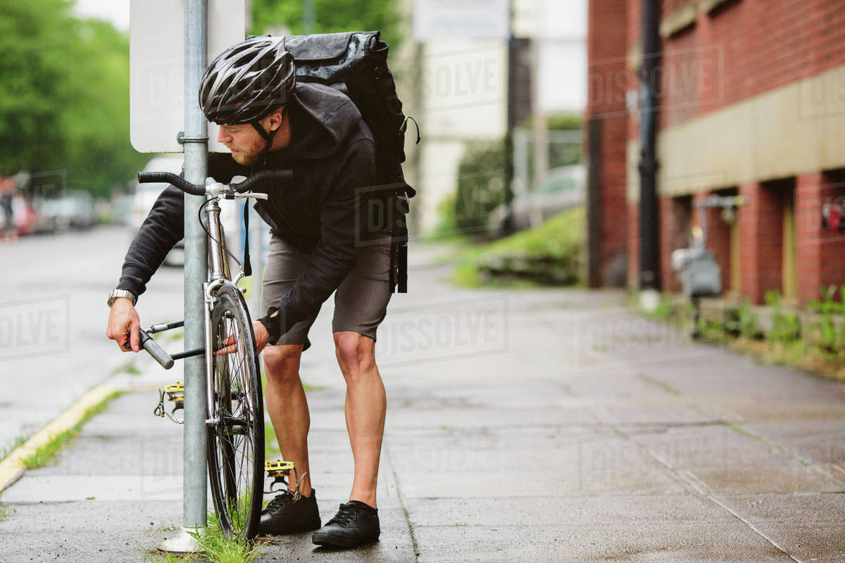 Ale commuter parking bicycle by pole while standing on wet footpath Royalty-free stock photo