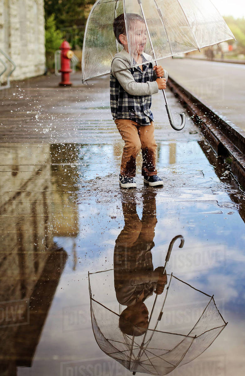 Playful boy with umbrella jumping on puddle at street Royalty-free stock photo