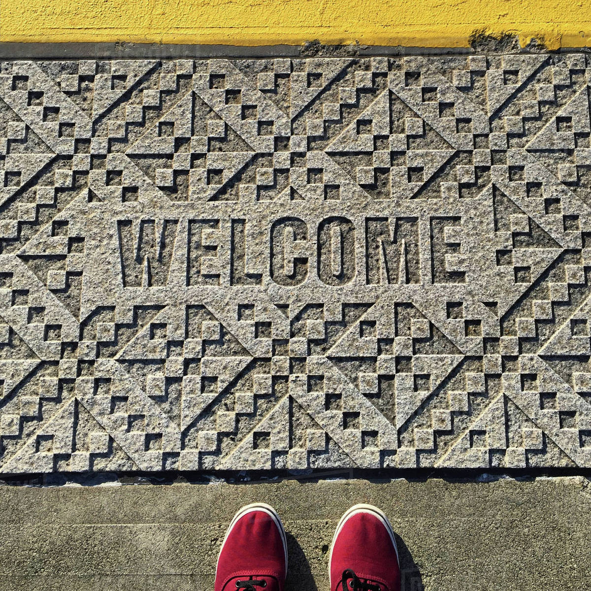 Low section of man standing by welcome text carved on footpath Royalty-free stock photo