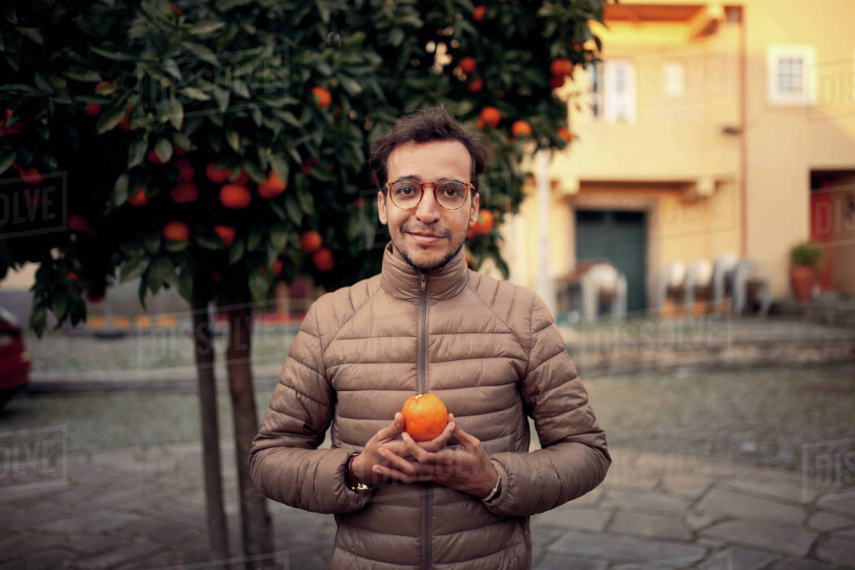 Portrait of man holding orange while standing against tree on footpath Royalty-free stock photo