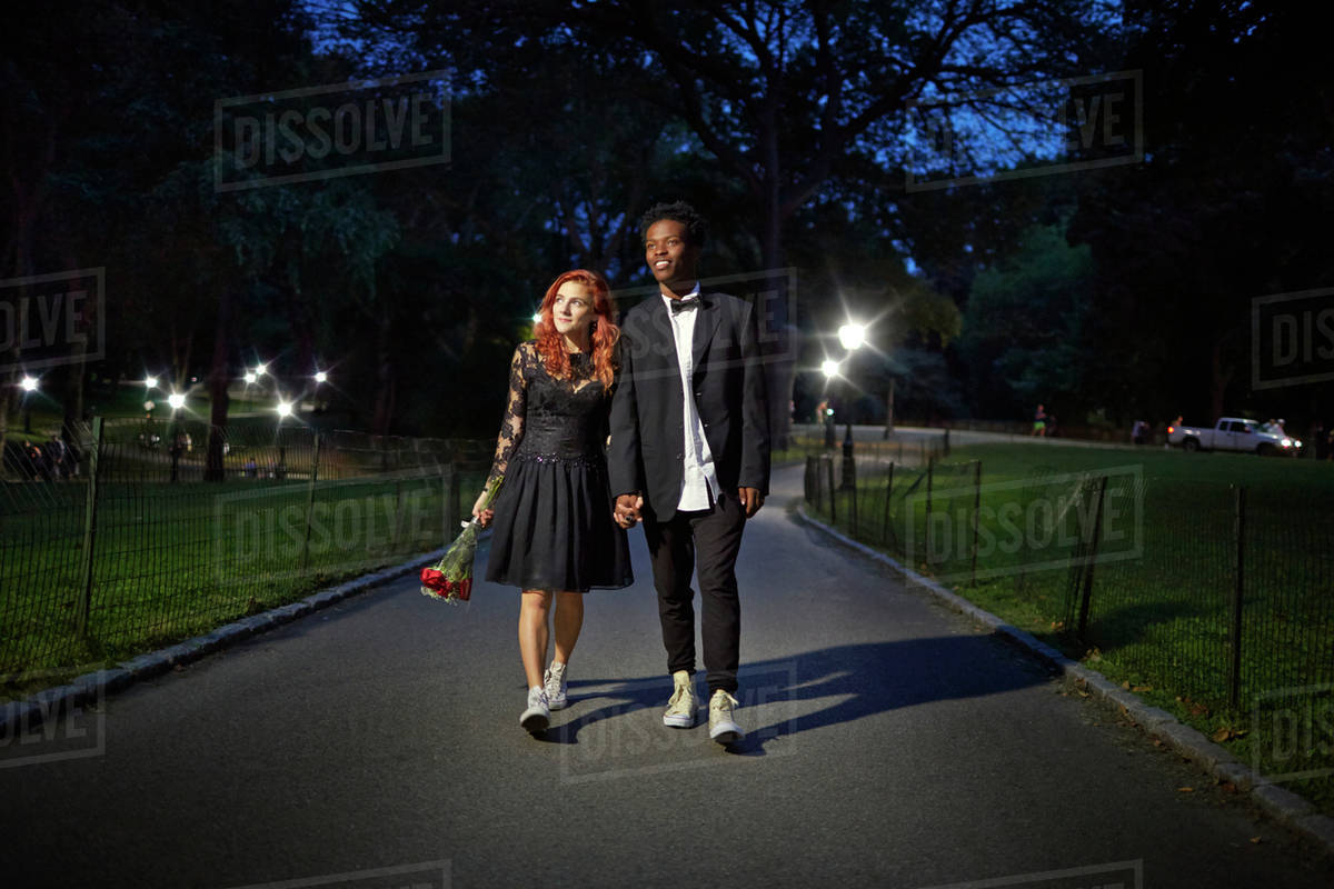 couple walking in park at night stock photo dissolve