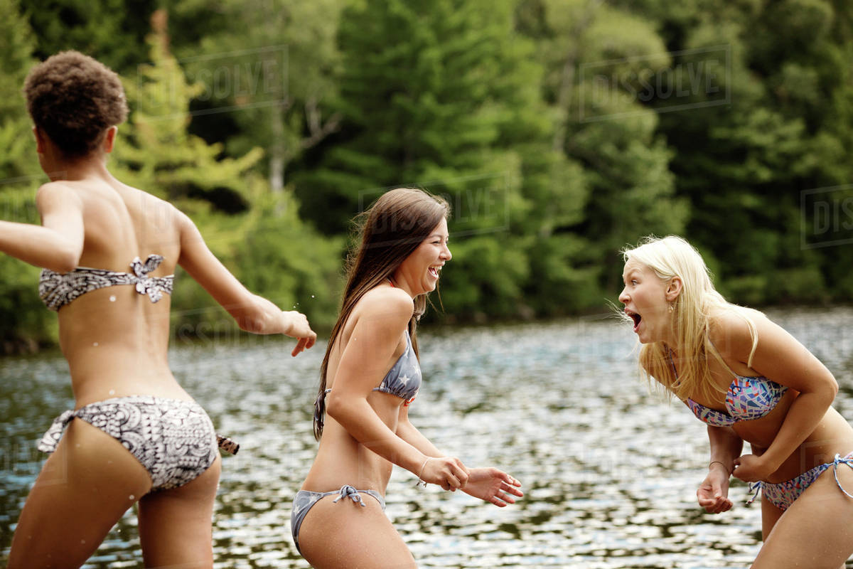 Teen Girls 16-17 With Young Woman Playing By Lake -2857