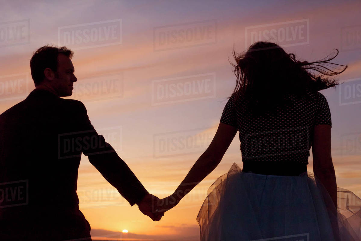 Rear view of couple holding hands against sky during sunset Royalty-free stock photo
