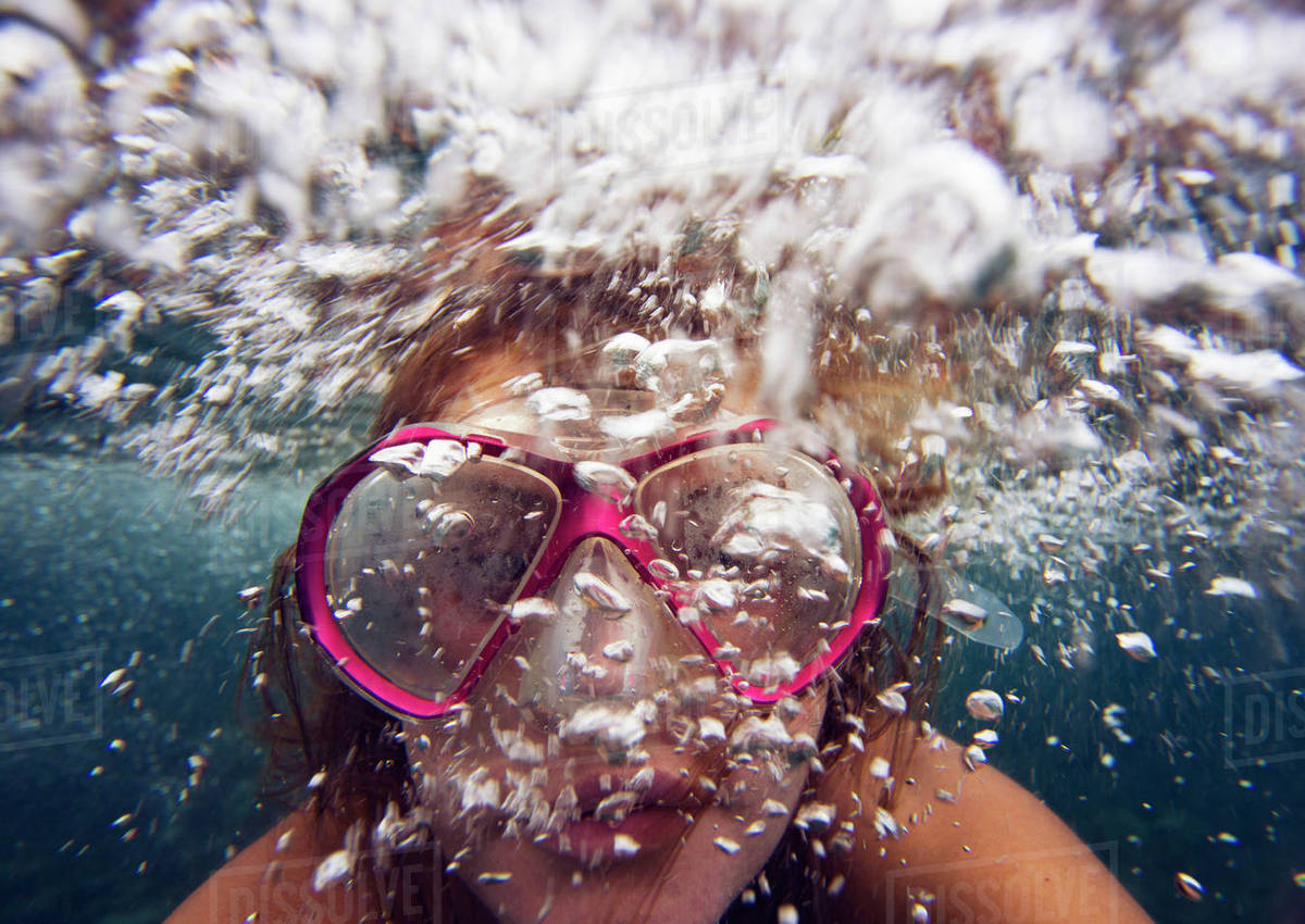 Close-up of woman wearing goggles swimming undersea Royalty-free stock photo