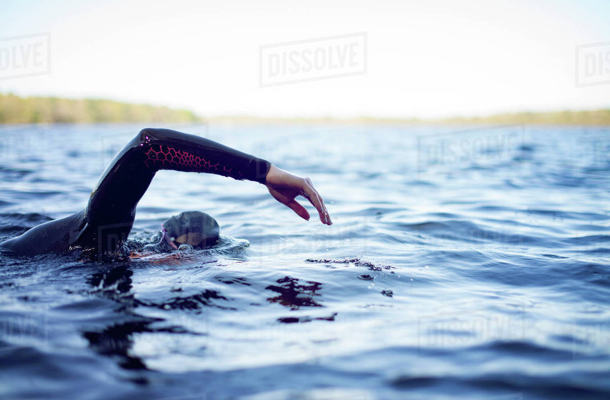 Cropped image of woman swimming in lake against sky Royalty-free stock photo