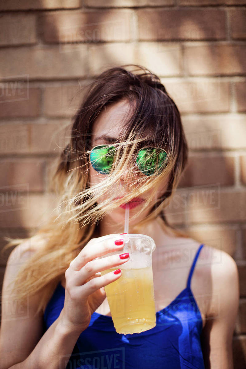 Portrait of woman drinking juice from disposable glass against wall Royalty-free stock photo