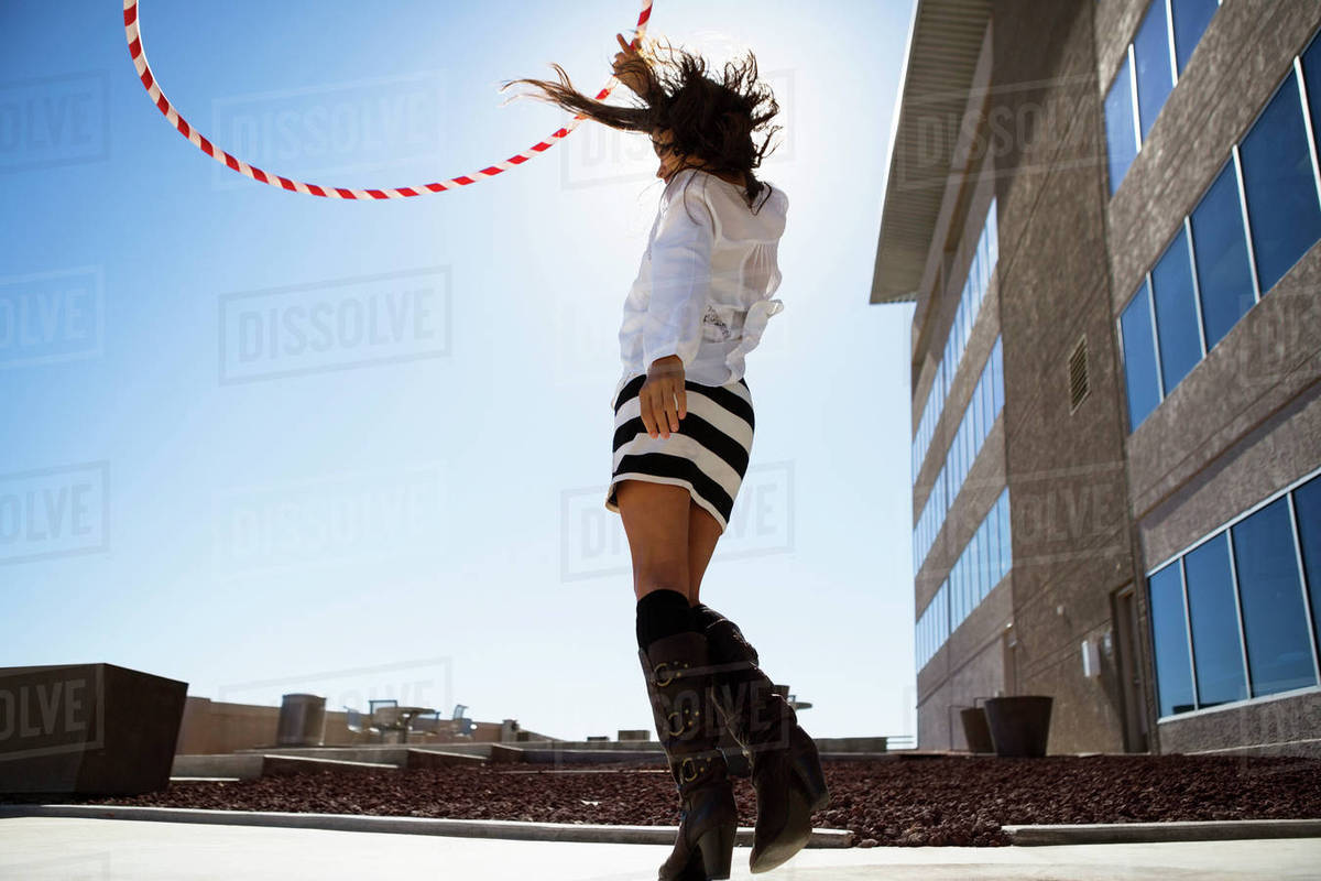 Woman playing with plastic hoop against clear sky Royalty-free stock photo