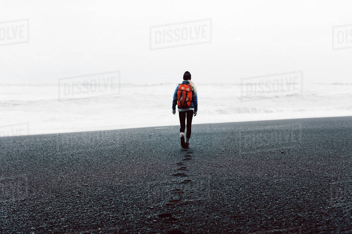 Rear view of woman walking on black sand beach against sky Royalty-free stock photo